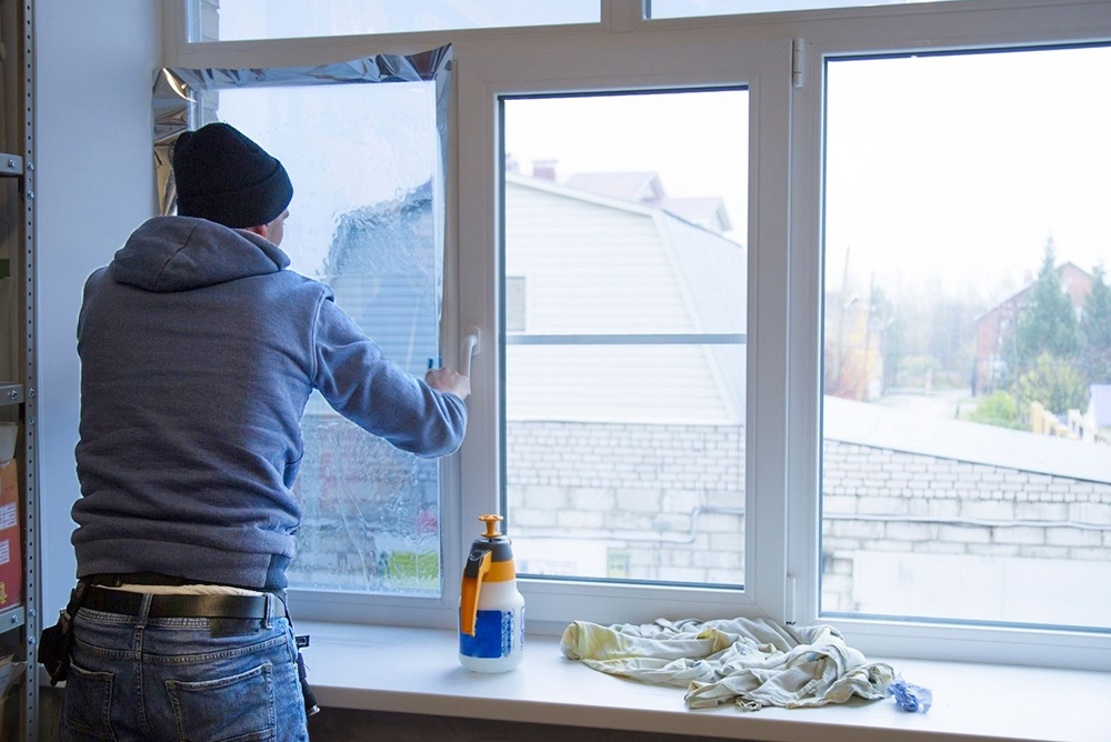 Man installing window film to protect home's windows before a hurricane.