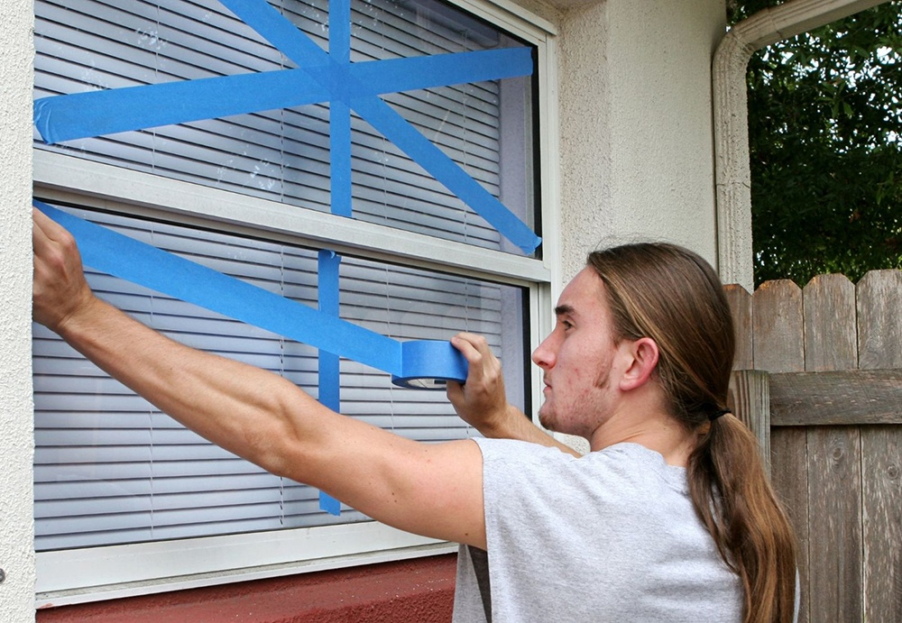 Using tape to protect your home windows from a hurricane is a bad idea. Man taping his window.