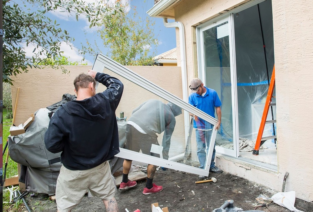 Workmen installing impact glass on a South Florida home.