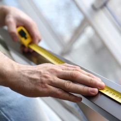 Man measuring metal railing, closeup. Construction tool